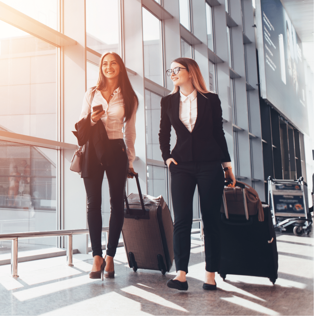 Two smiling women walking through airport with suitcases