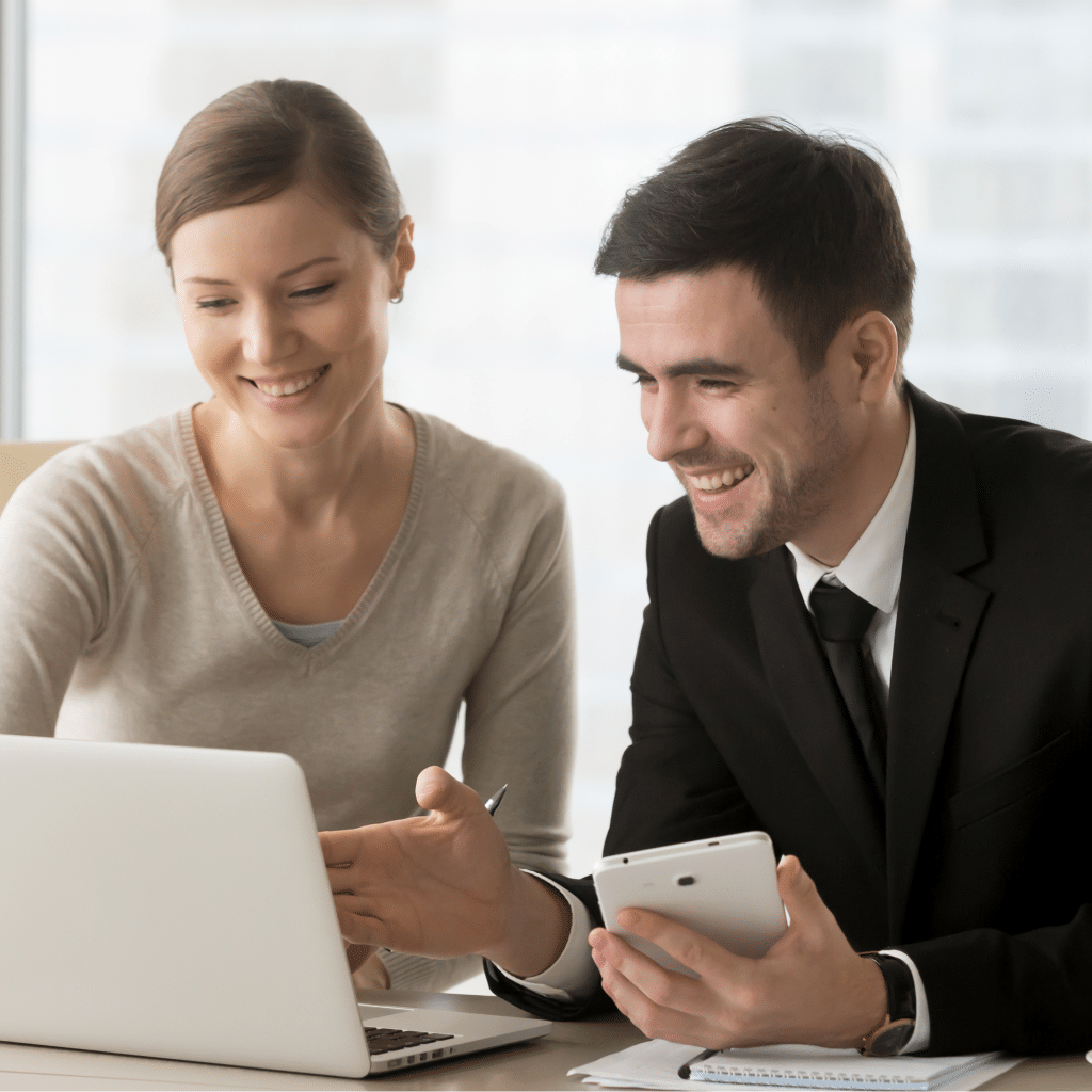 Smiling woman showing smiling man something on laptop